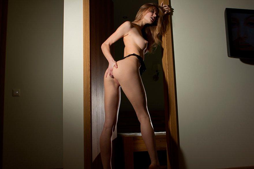 Чистенькая модель со свелыми волосами снимает нижнее белье в дверном проеме секс фото