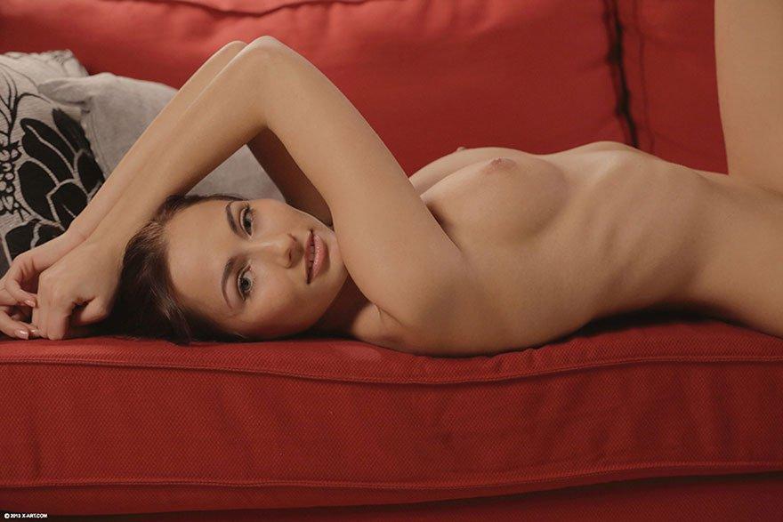 Эротические фото молоденькой брюнетки на красном диване