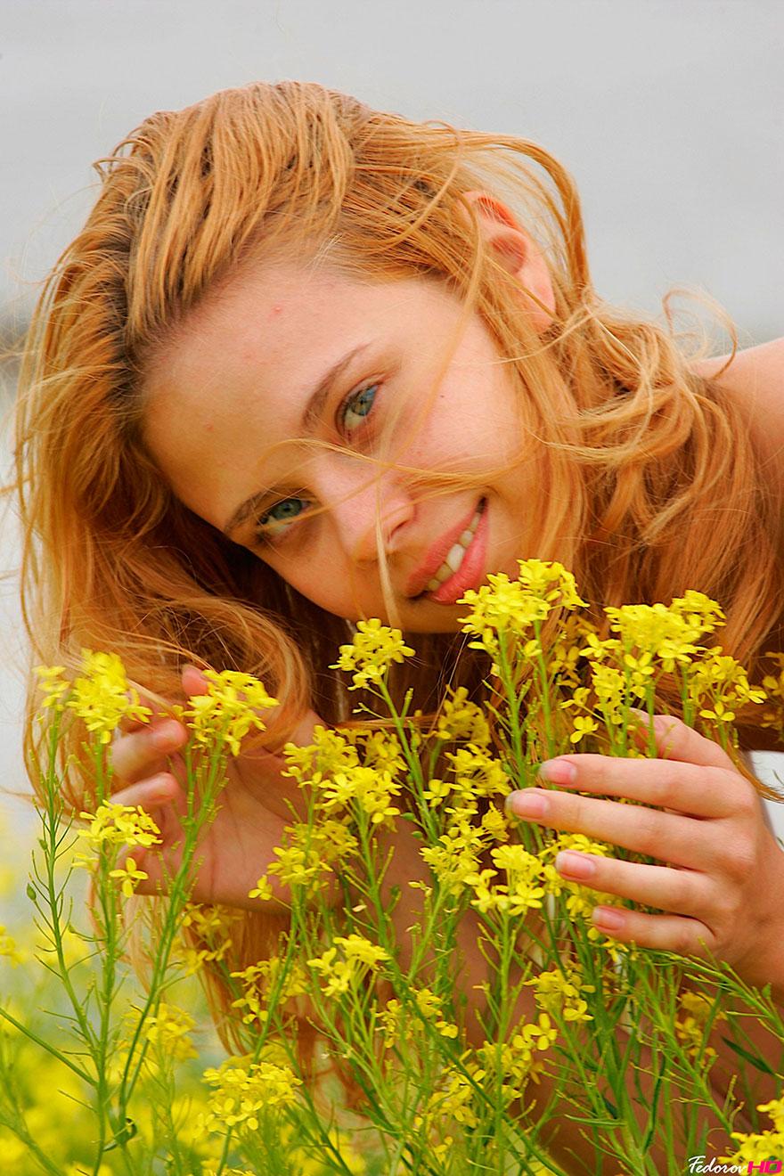 Молоденькая рыжая девушка голая среди желтых цветов