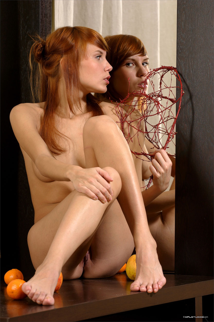 Худенькая рыжая девушка перед зеркалом - фото эротика