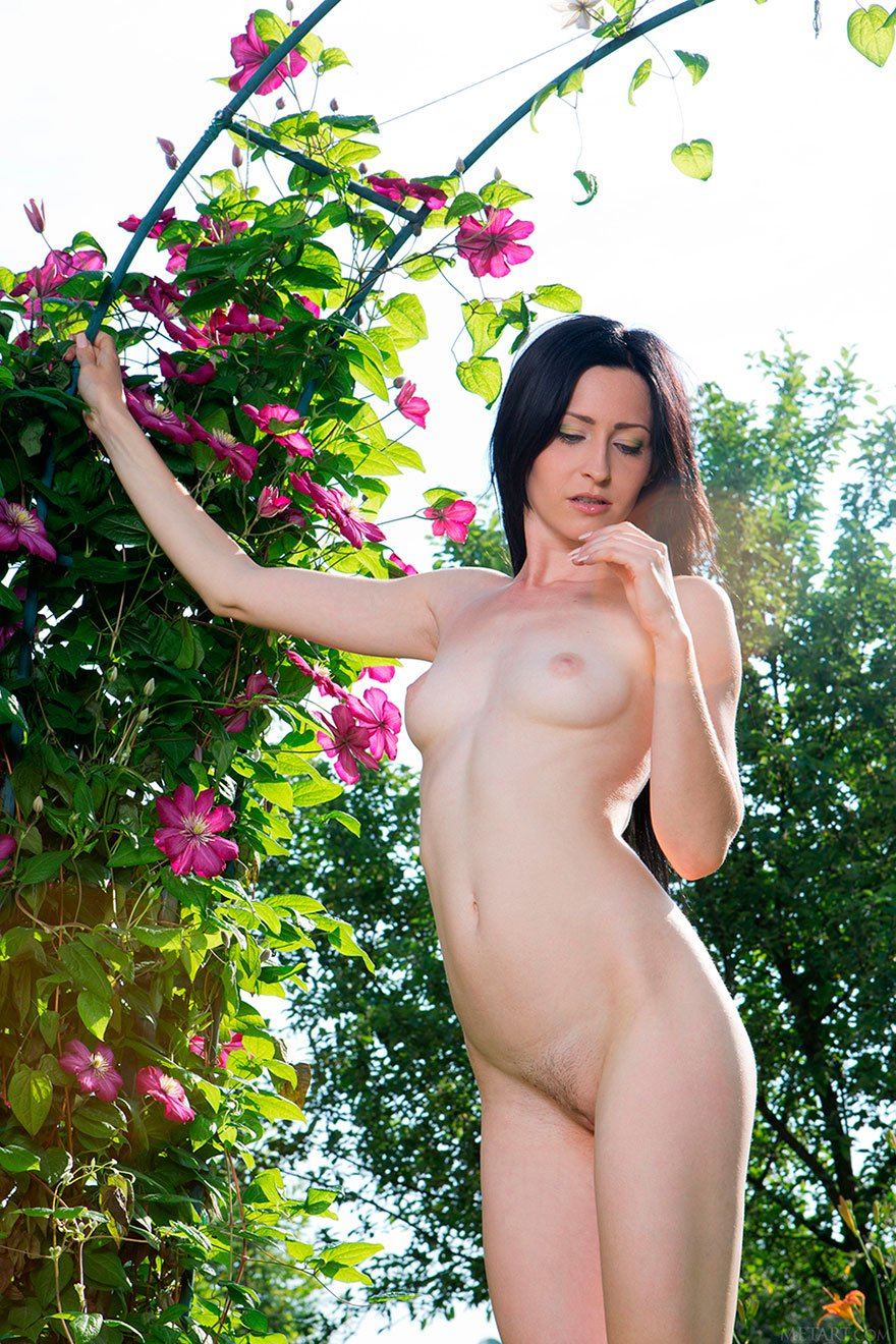 Синеглазая темненькая девушка в роскошном парке с классными цветами