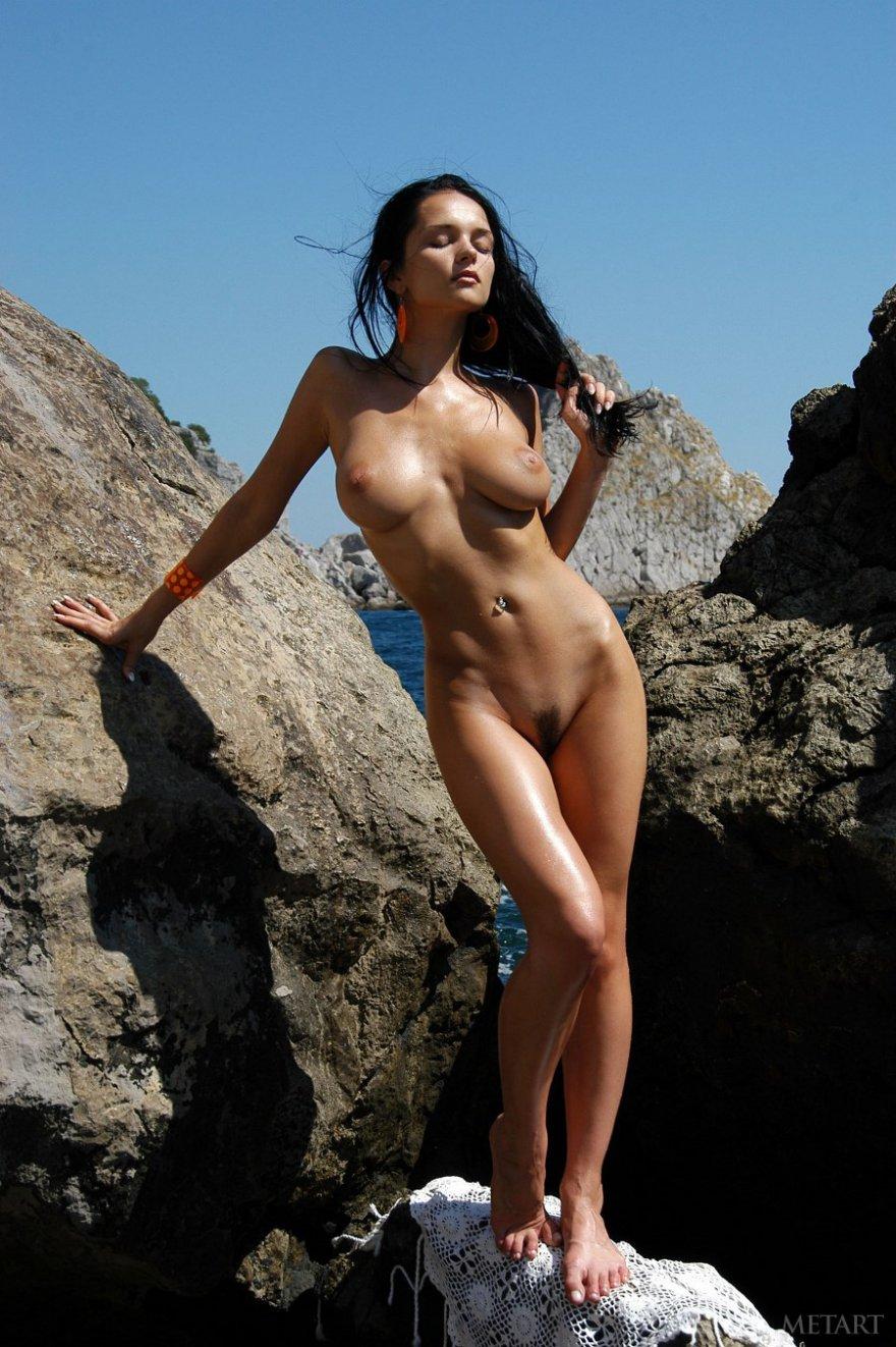 Грудастая брюнетка голая на камнях
