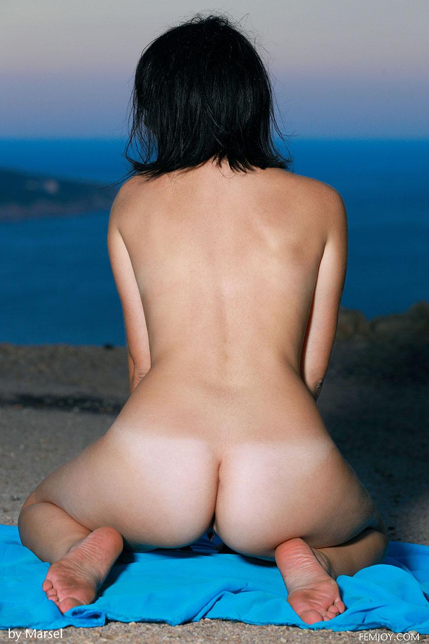 Стройная брюнетка отдыхает на берегу моря