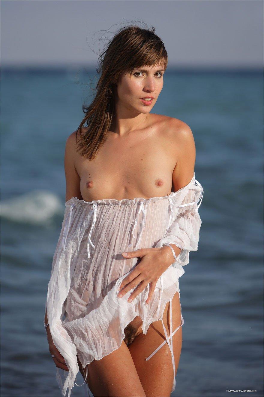 Эротические фото молодой девушки в белой тунике на море
