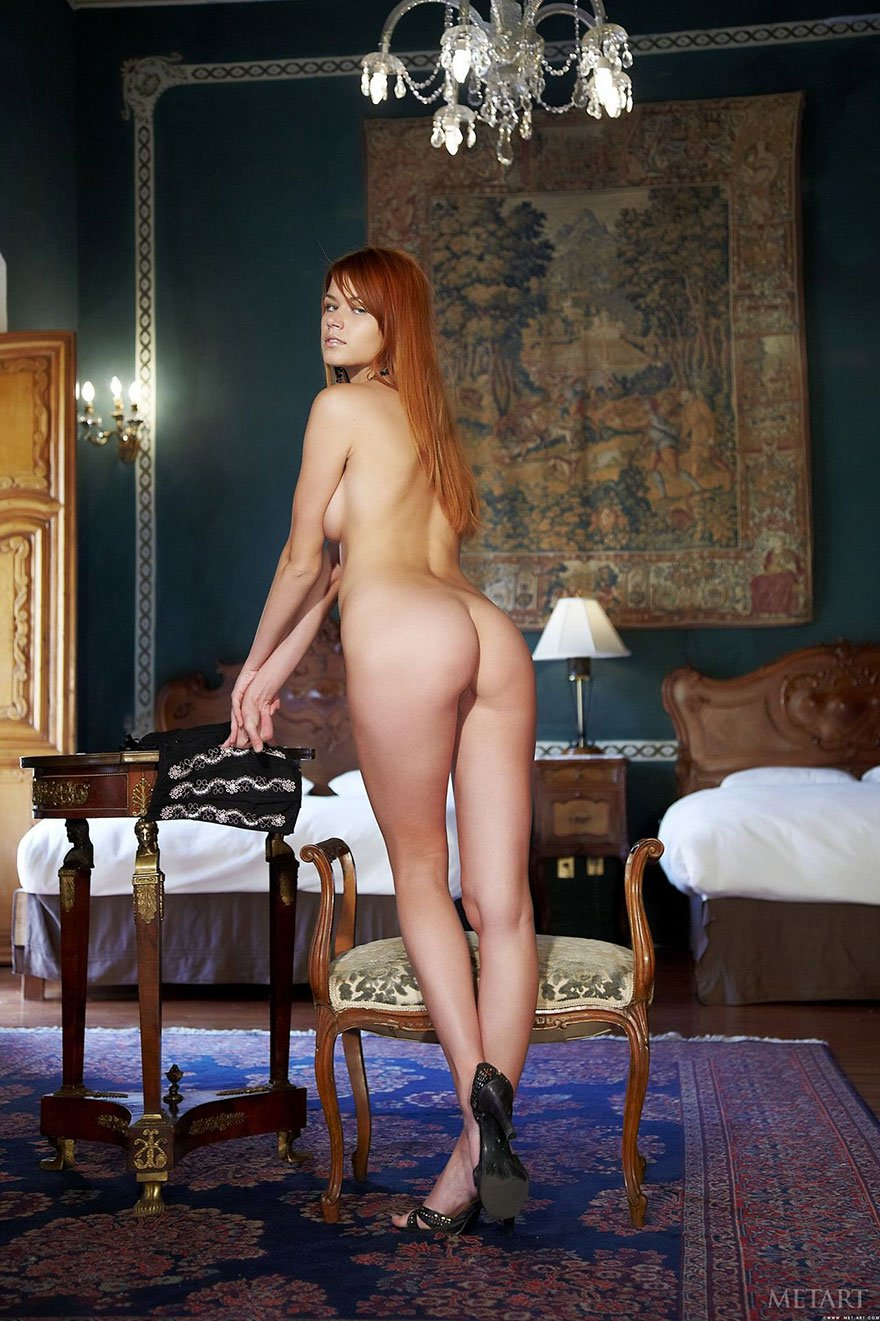 Рыжеволосая девица раздевается в красивой спальне