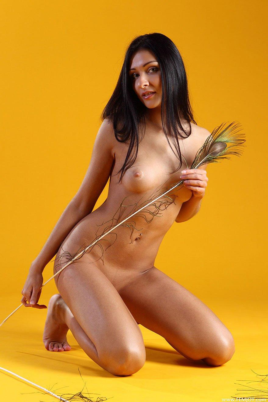 Прекрасная темноволосая девка снимается раздетая с пером павлина