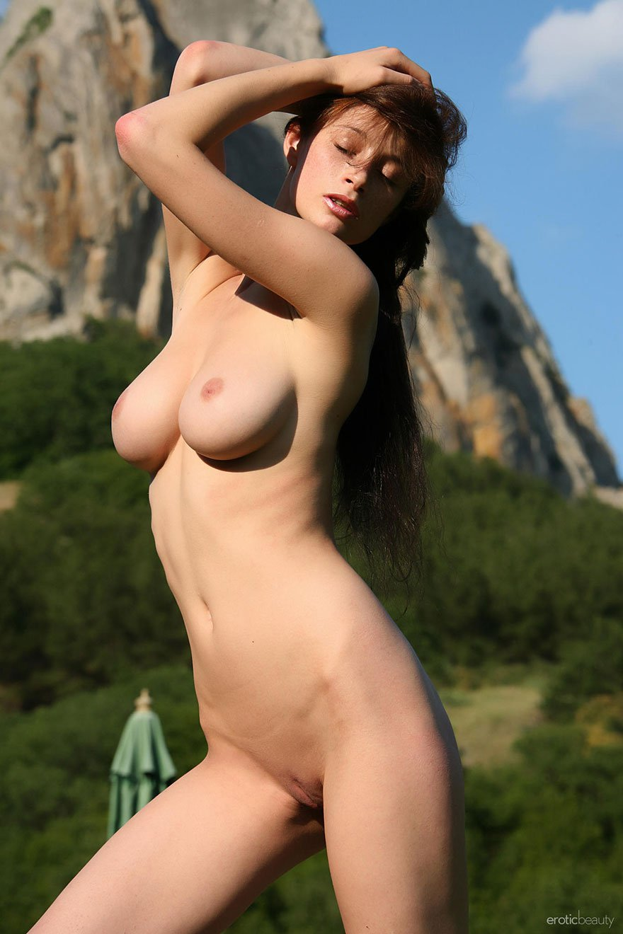 Русая порноактрисса с крутыми сиськами нагая в цветнике