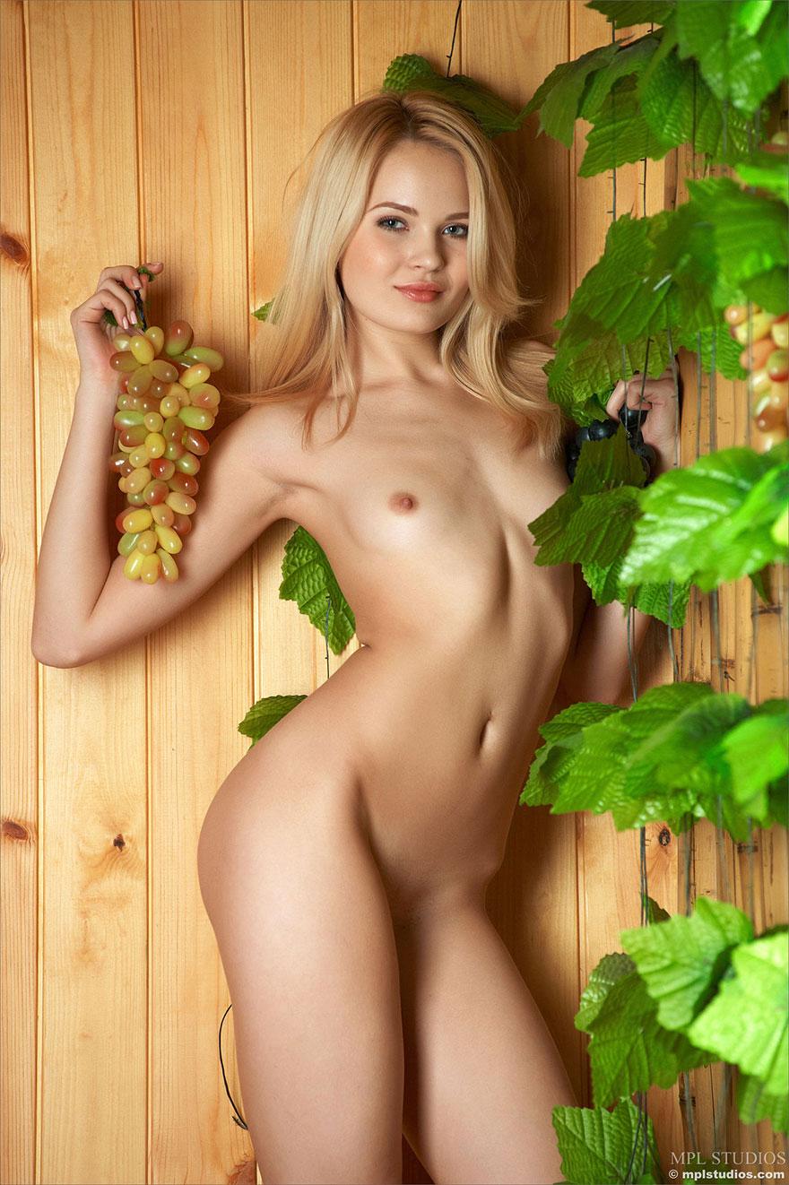 Красивая модель позирует с виноградом
