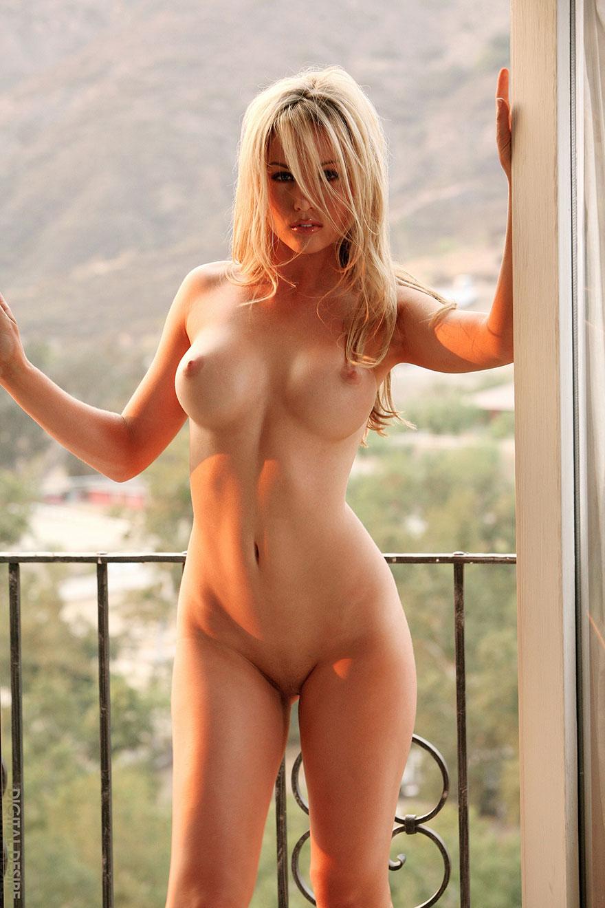 Сексуальная блондинка в кружевном белье стоит у окна