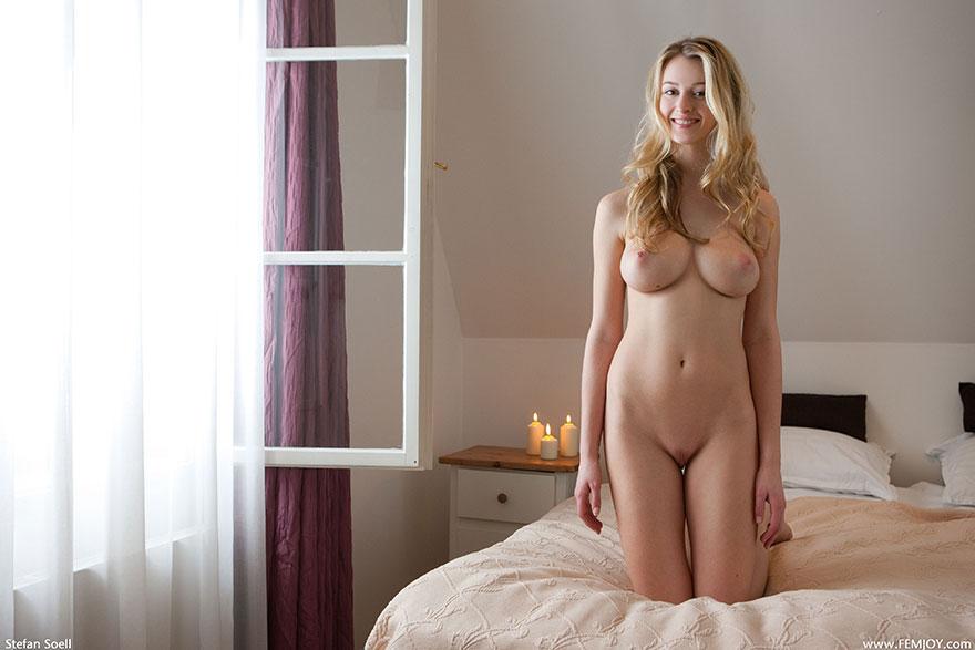 Голая блонди с красивой грудью у открытого окошка