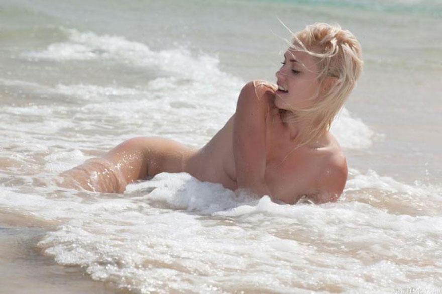 Голая блондинка с маленькой грудью эротично позирует на море