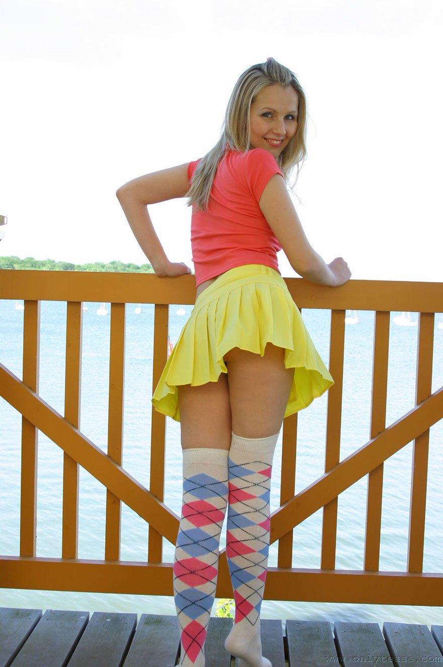 Молодая блондиночка в короткой юбочке снимается на мосту
