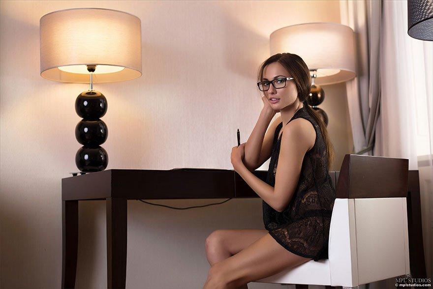 Роскошная милашка в очках сидит за столом