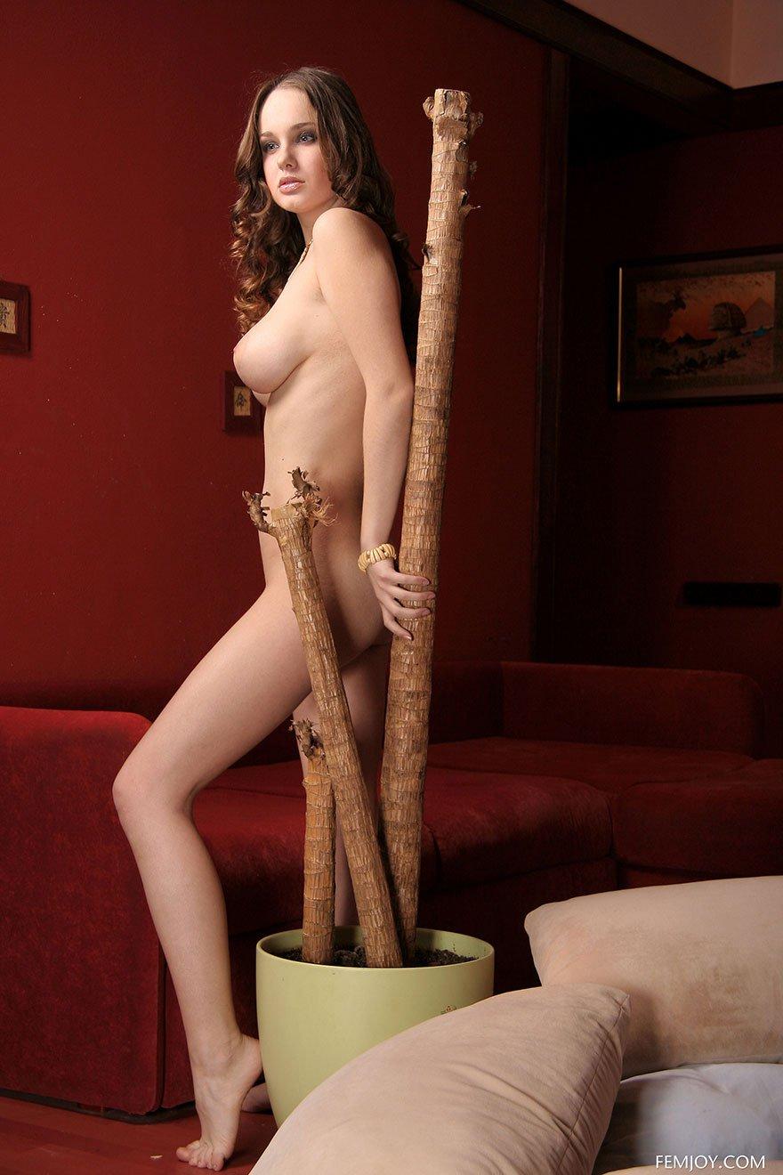 Голая девушка с красивой грудью позирует в гостиной