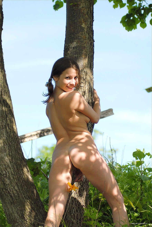 Молоденькая девушка раздевается под деревом