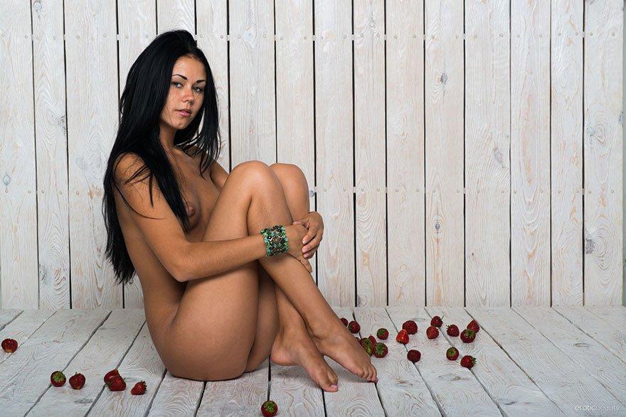Модель с темными волосами с роскошными волосами ест клубнику