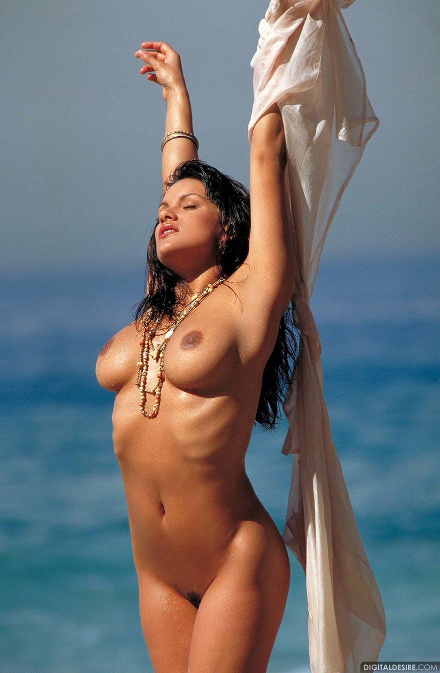 Красивая грудастая брюнетка на пляже