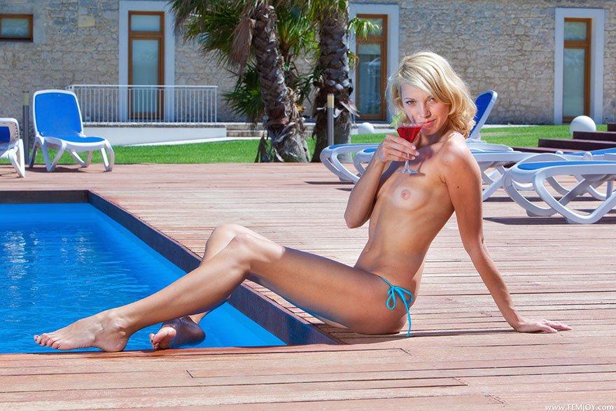 Блондинка в голубом купальнике загорает возле бассейна