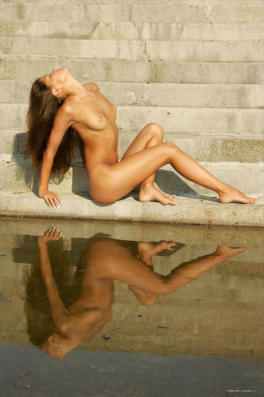 Загоревшая обнаженная девка на каменных ступенях