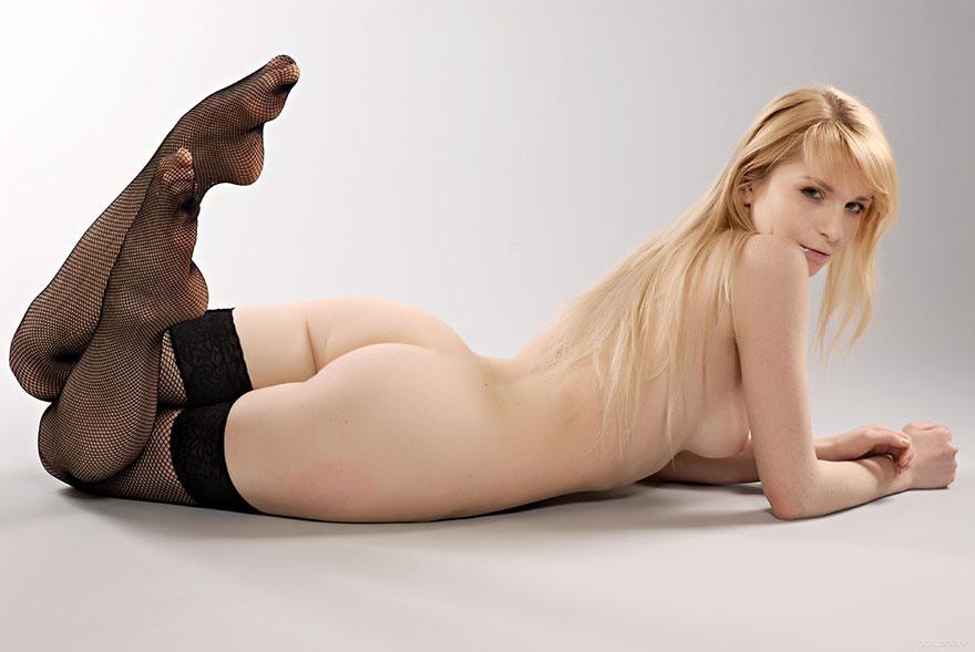 Блондинка в чулках в сеточку позирует в студии