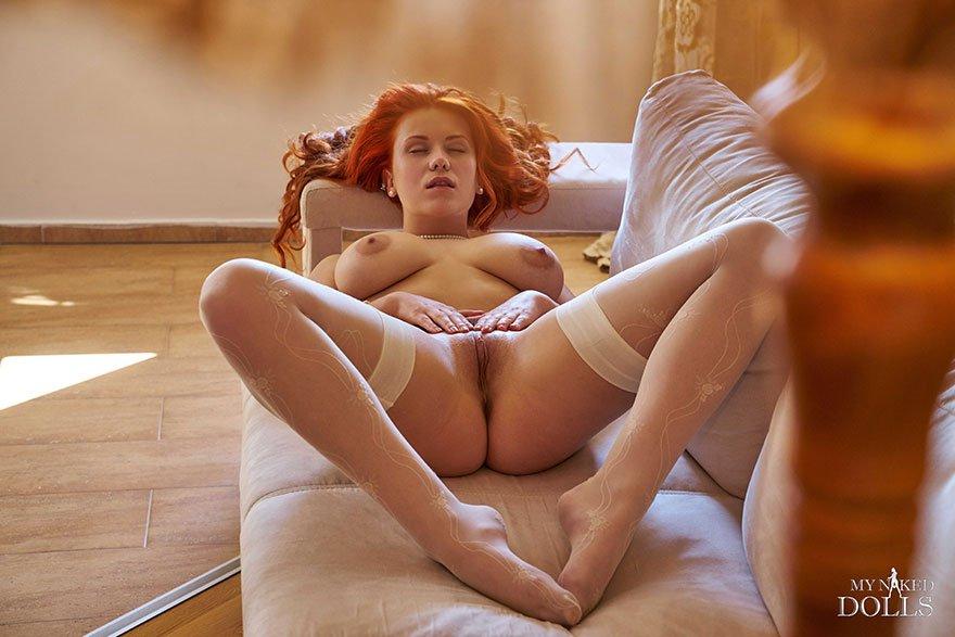 Рыжая красотка с большими сиськами позирует в чулках