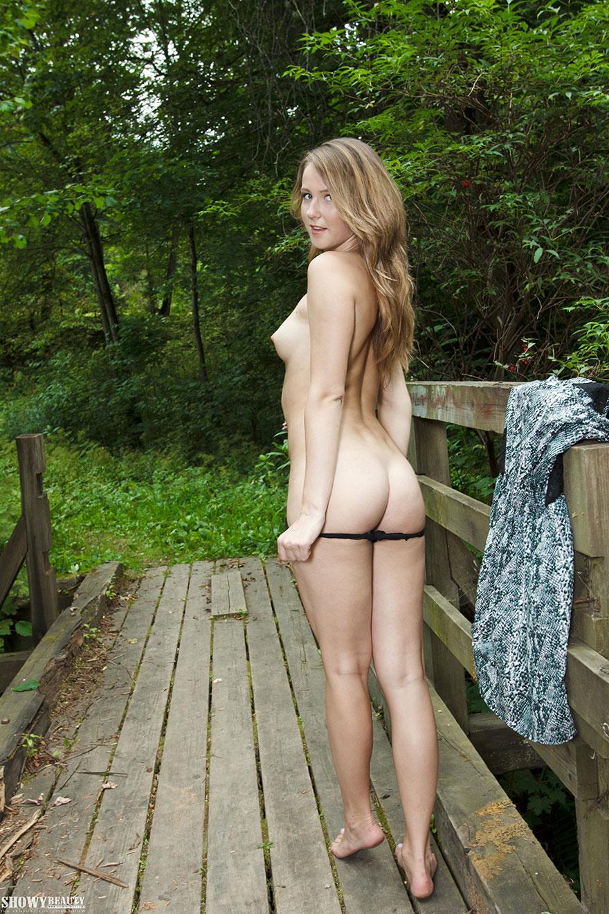 Юная девушка раздевается на мосту - фото ню