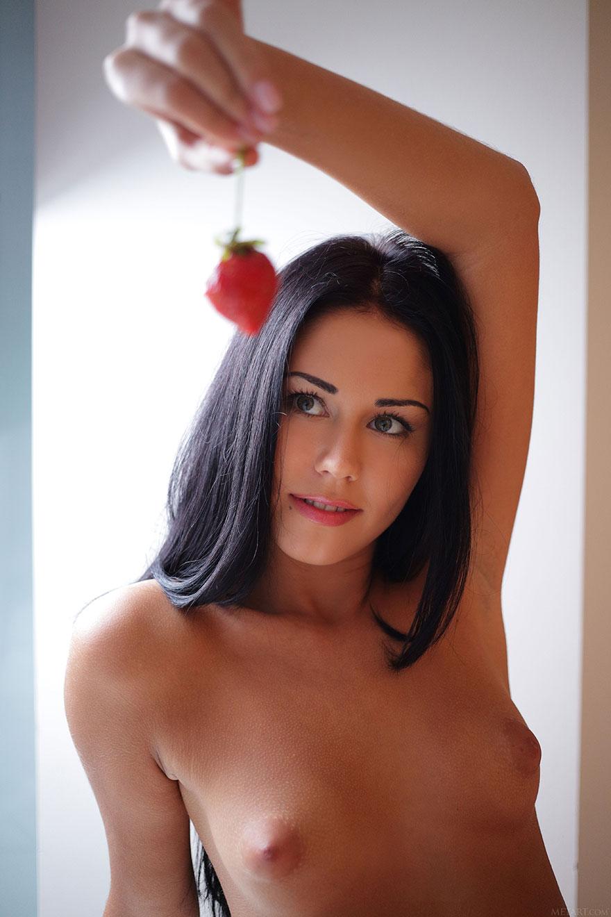 Красивая брюнетка с маленькой грудью ест клубнику
