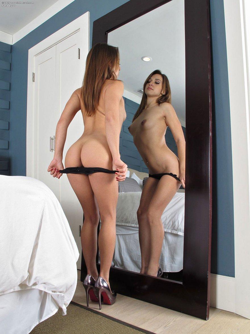 Молодая девица снимает лифчик перед зеркалом