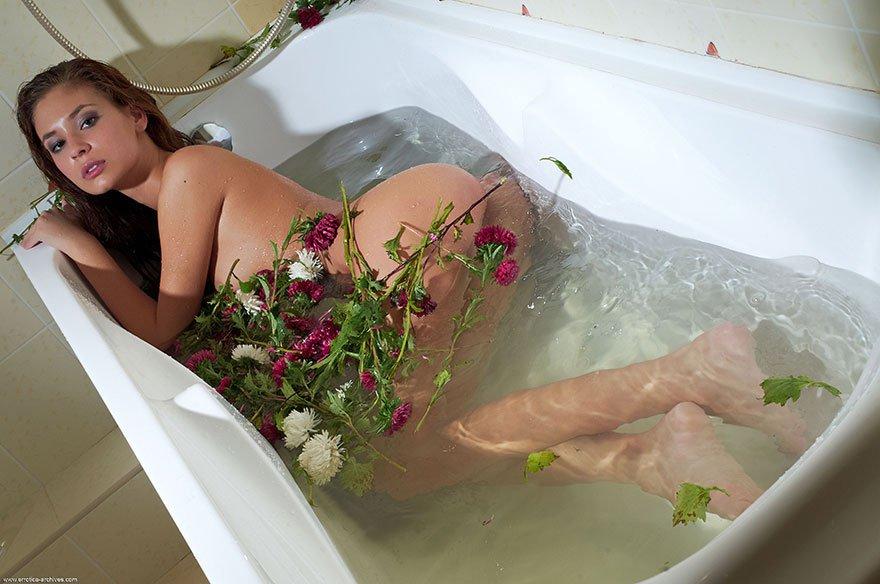 Голая девушка в ванне с цветами