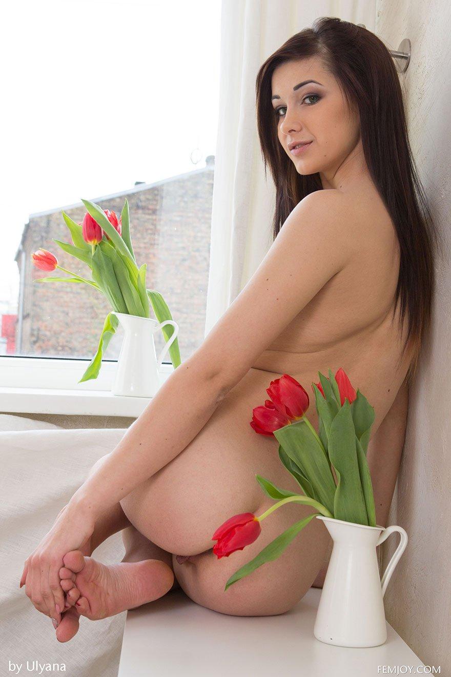 Чика позирует обнаженная с букетом тюльпанов