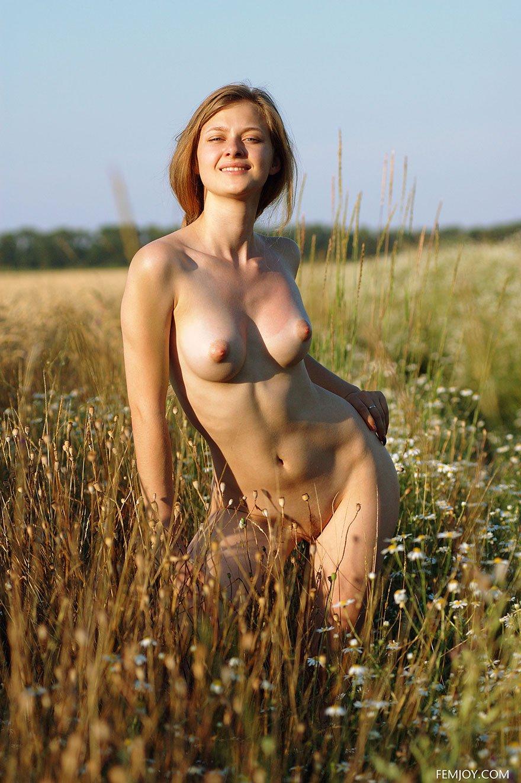 Молоденькая рыжая девушка в поле с букетом ромашками