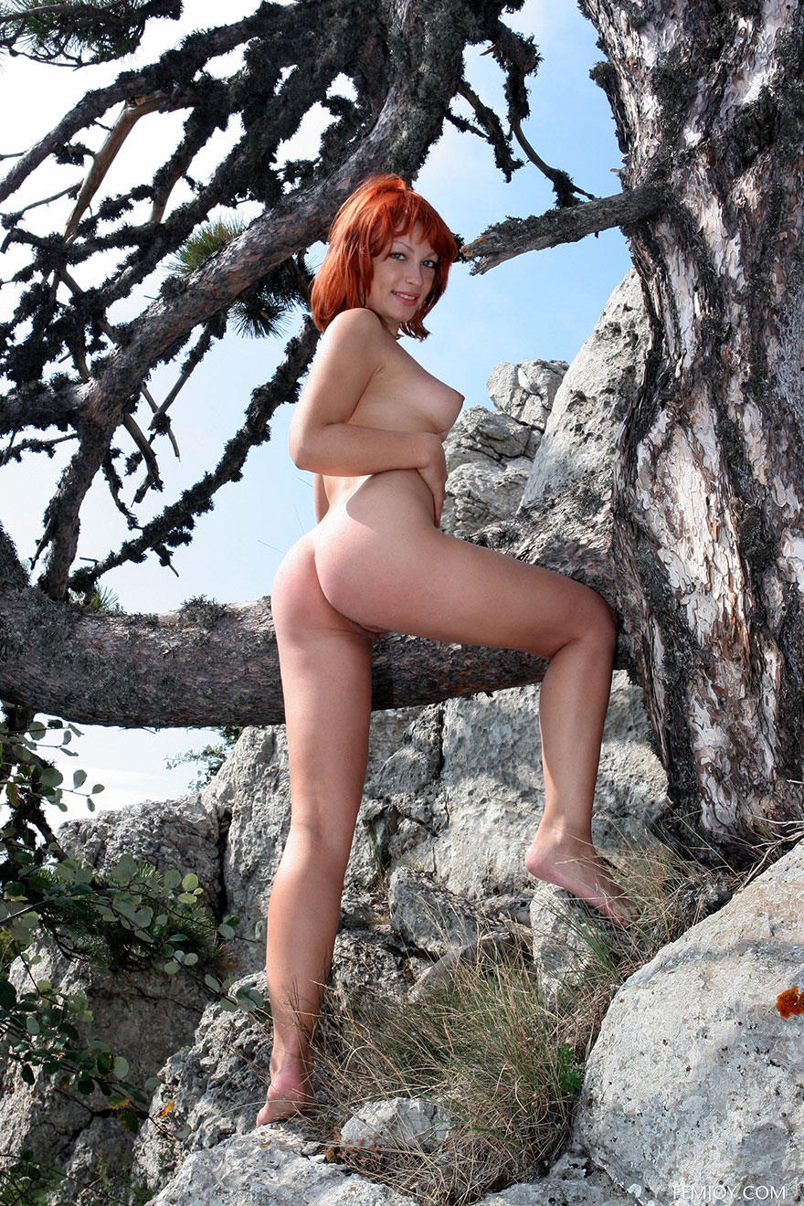 Рыженькая красавица снимается раздетая на дереве