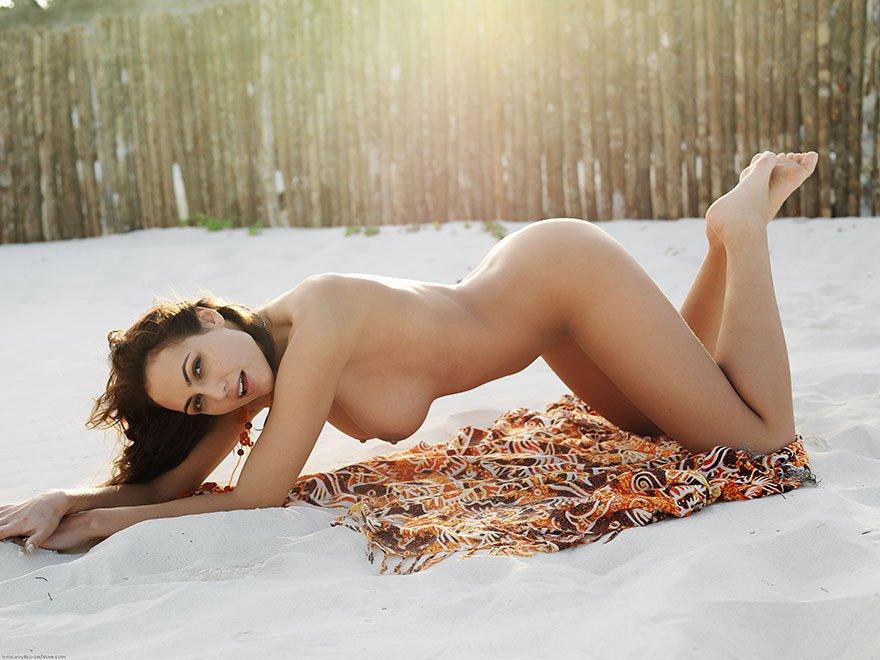 Загорелая шатенка с красивой грудью позирует на белом песке