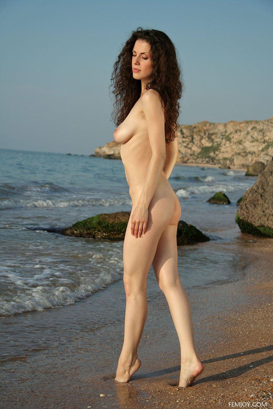 Молодая девушка в короткой юбке гуляет по берегу моря
