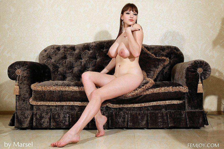 Шикарная красотка с большими сиськами позирует в гостиной