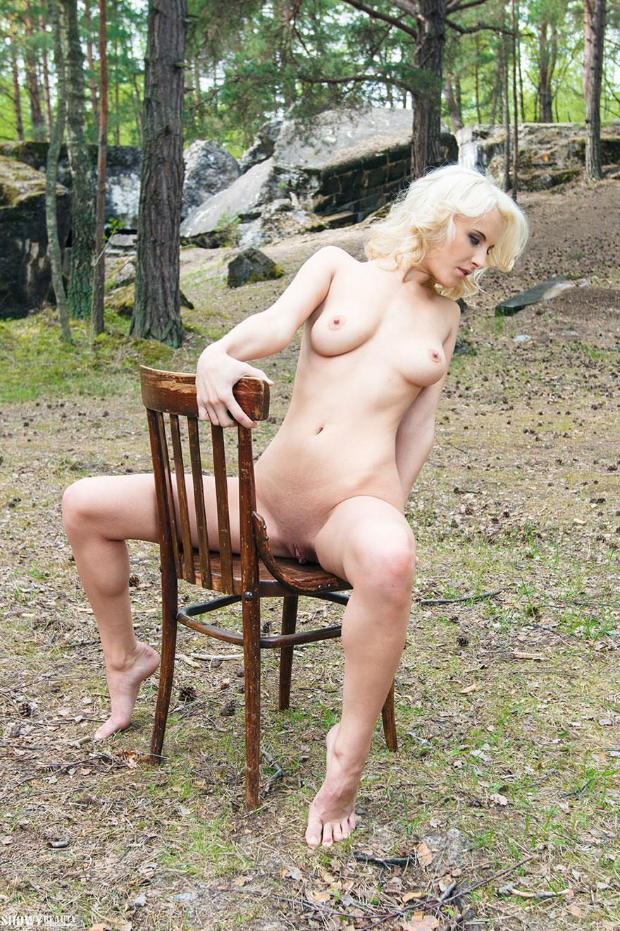Светловолосая девушка в свитере на голый торс красуется около дерева