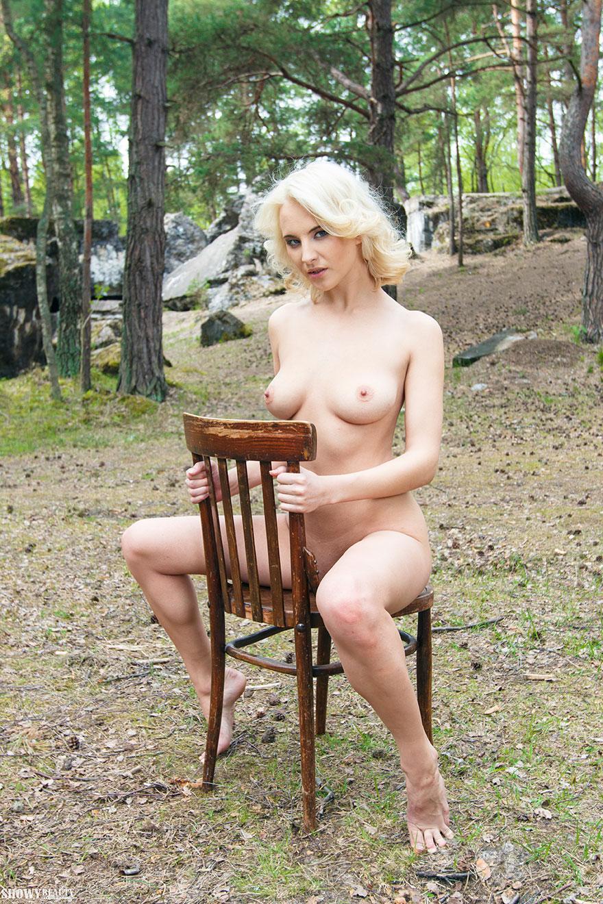 Блондинка в свитере на голое тело позирует в лесу