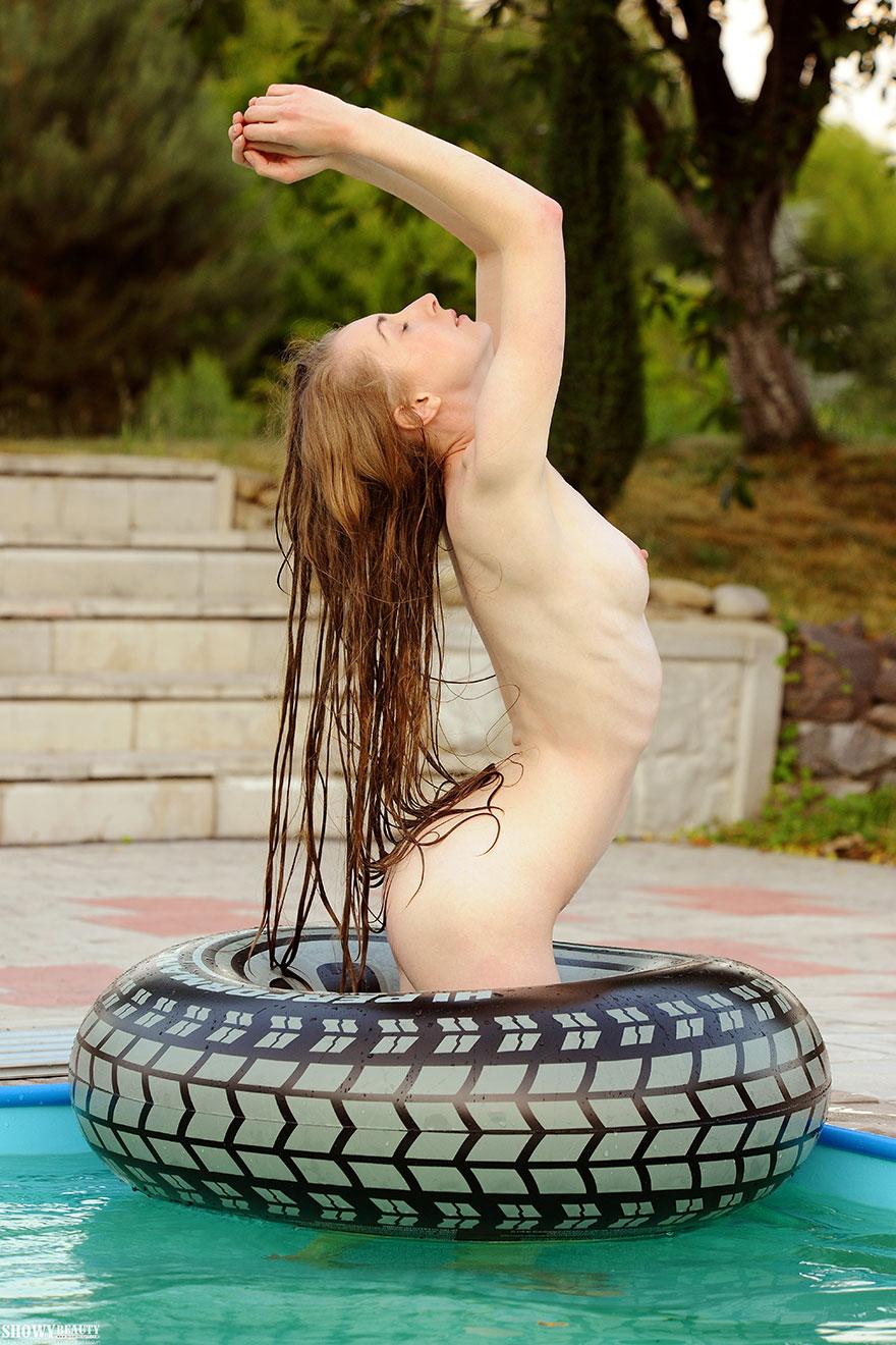 Молодая девушка с маленькой грудью плавает в бассейне