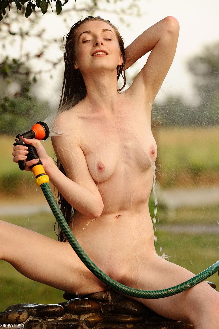 Шатенка с длинными волосами поливает свое голое тело из шланга