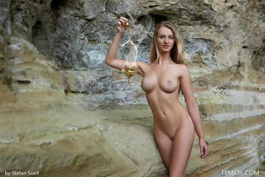 Привлекательная клубничка раздетой блондиночки с ароматической лампой на фоне скалы