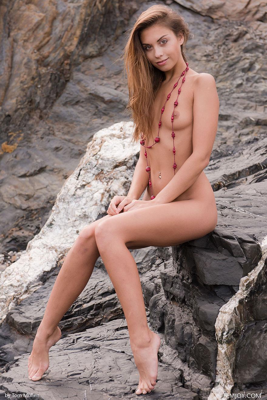 Порнуха ухоженной модели с красными бусами на шее среди скал
