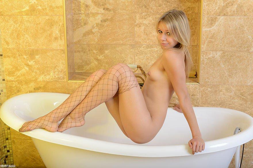Блондинка с маленькой грудью позирует в чулочках