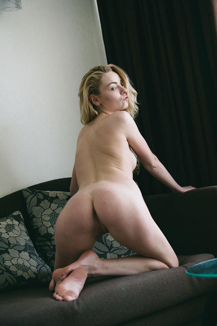 Молоденькая блондинка с голубыми глазами позирует на диване