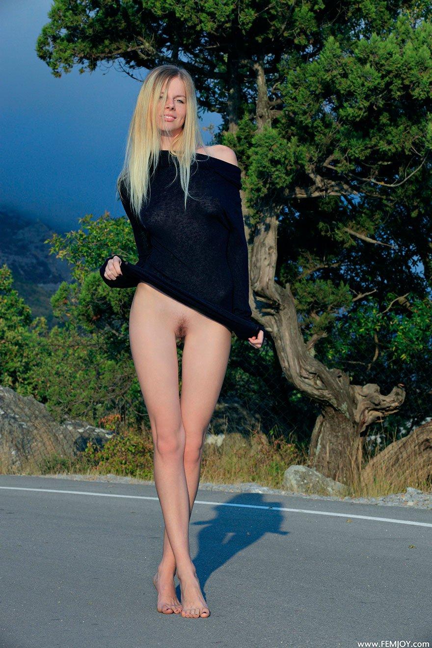 Голая блондинка с тонкой талией позирует на дороге