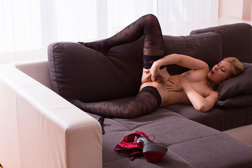 Блондинка в чулках мастурбирует на диване