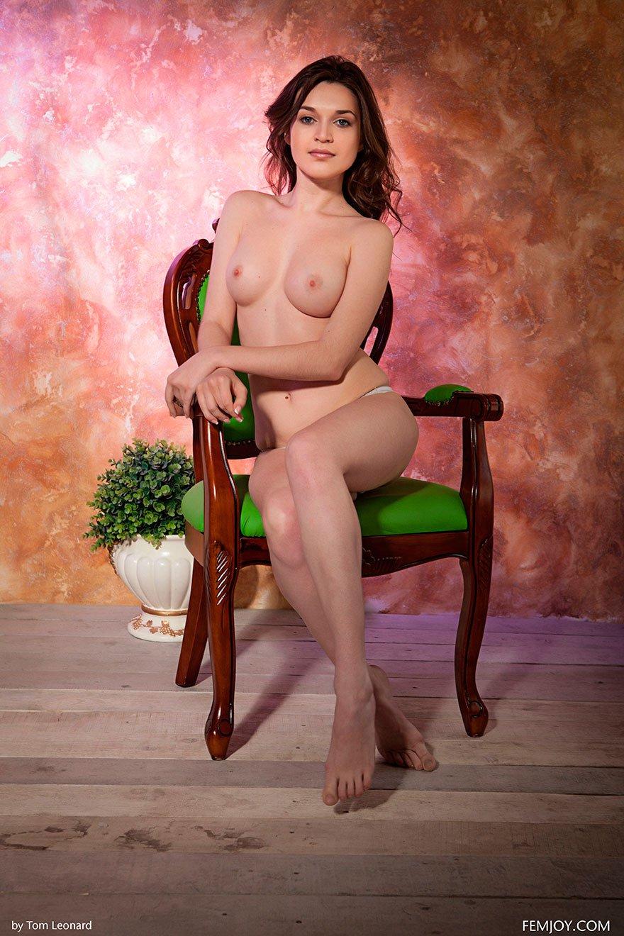 Красивая девушка с голубыми глазами сидит на зеленом стуле
