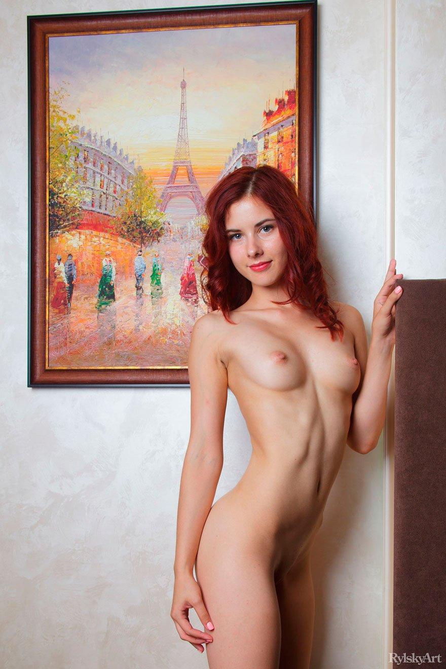 Раздетая рыжая модель на фоне картины