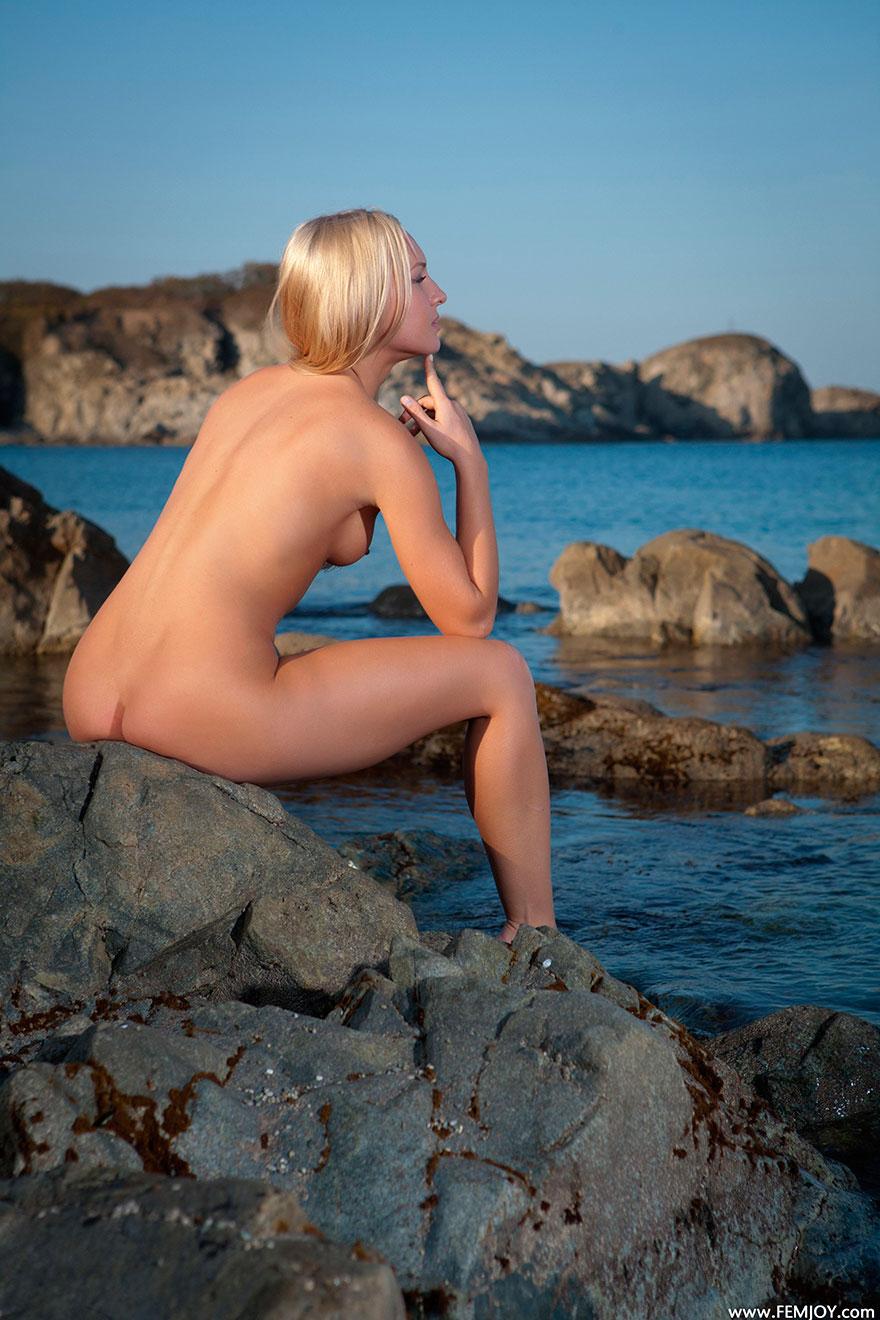 Голая блондинка на скалистом морском берегу