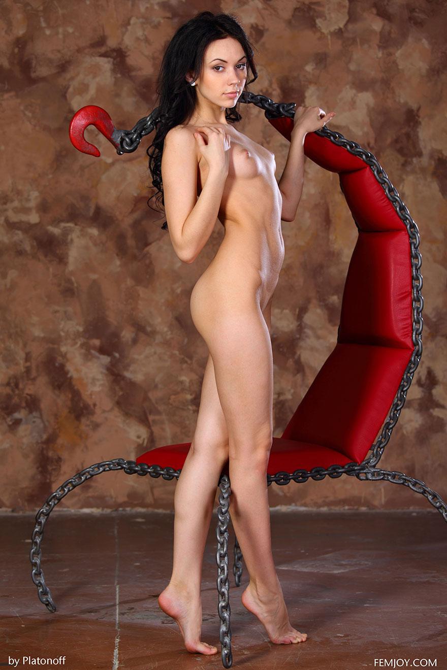 Красивая брюнетка с маленькой грудью позирует в красном кресле