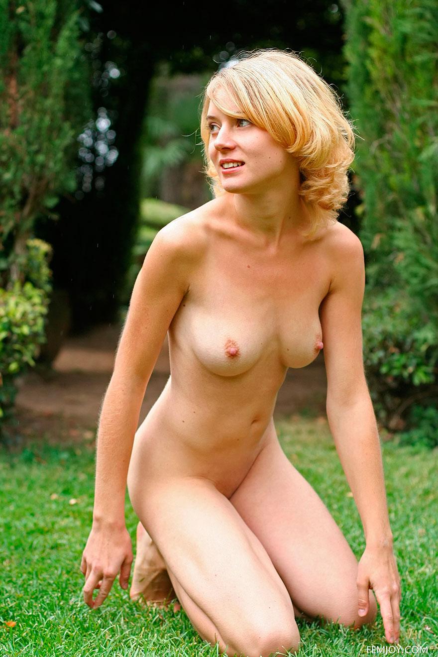 Голая блондинка с красным шарфом в саду